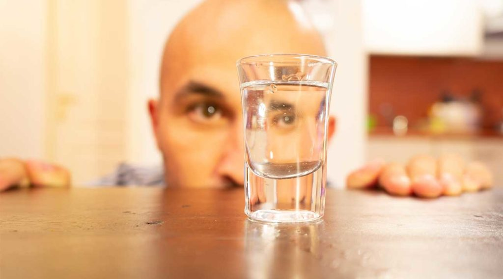 alcohol addiction man staring at a shot glass on a table