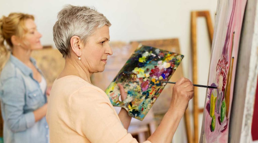 Woman painting a picture participating in Art Therapy