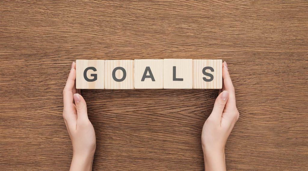 woman holding wooden blocks that spell out the word goals