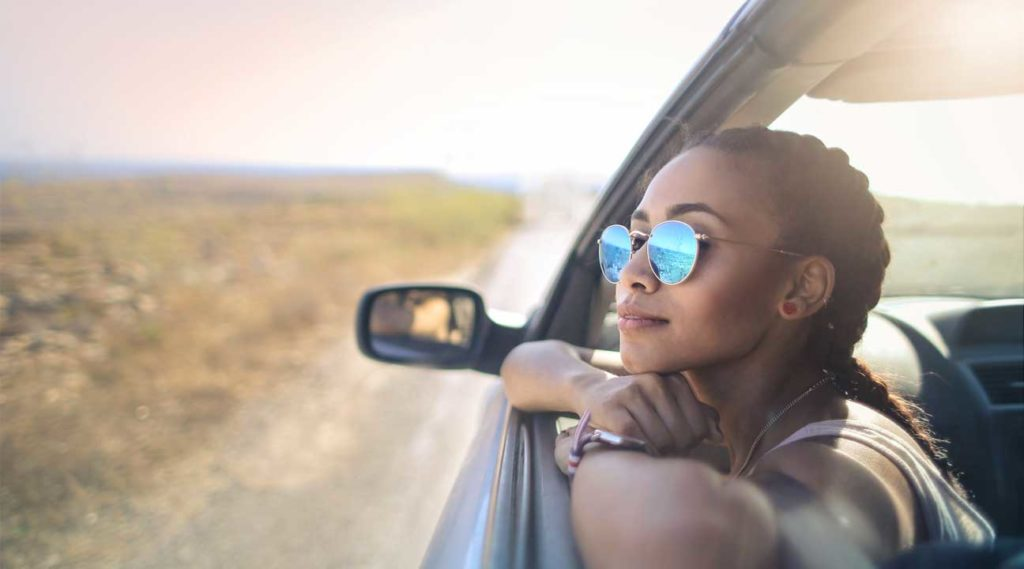 young woman wearing glasses looking out of a car window on a sunny day