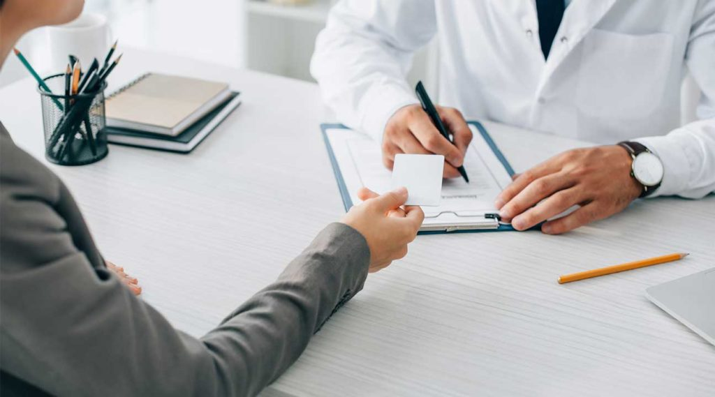 woman handing her doctor her Aetna insurance card