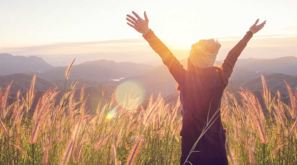 woman holding up her arms during sunrise celebrating her sobriety